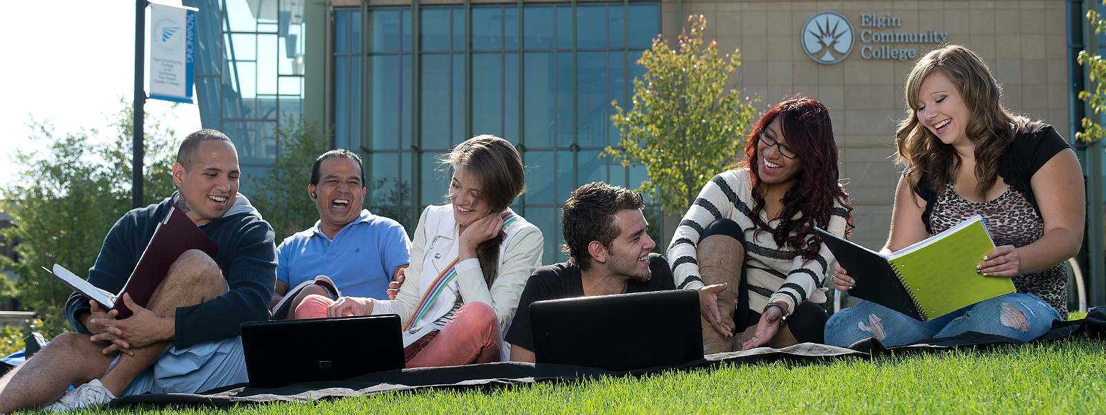Students that are enjoying sitting on lawn in front of Building C.