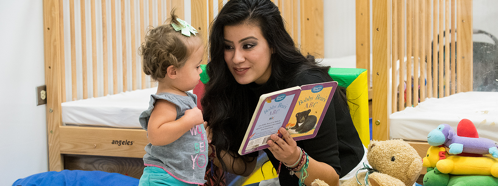 Toddler being read to by ECC staff.