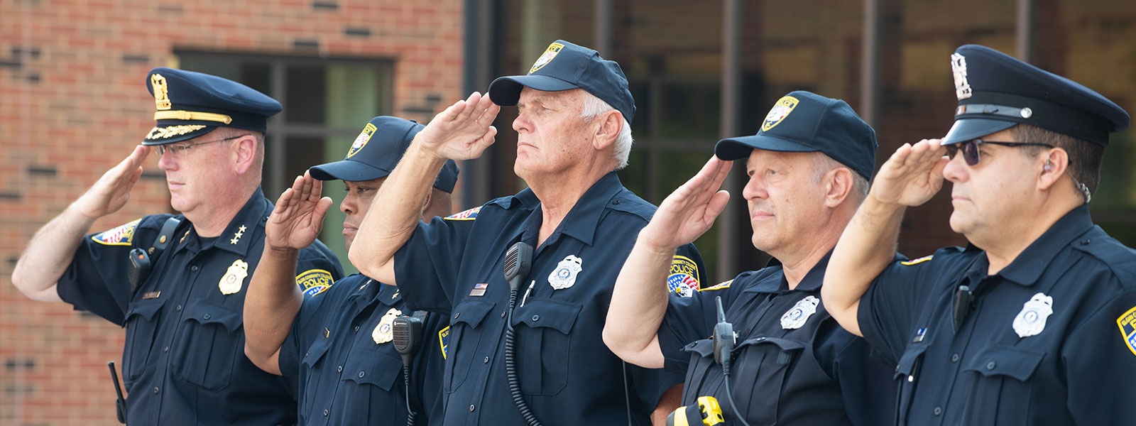 Elgin CC Police Department Officers salute during the color guard presentation of flags.